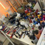Zeigt den Arbeitstisch des Künstler mit viel Farben, Pinsel und Sparte